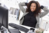 Beautiful businesswoman stretching at desk smiling
