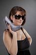 coole junge Frau mit Sonnenbrille präsentiert Schuh