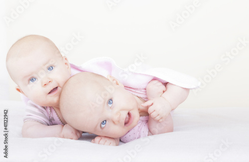 identical twin sister on bed learning how to crawl