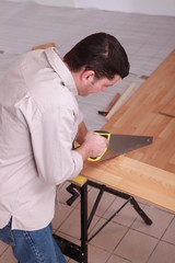 Man sawing plank of parquet
