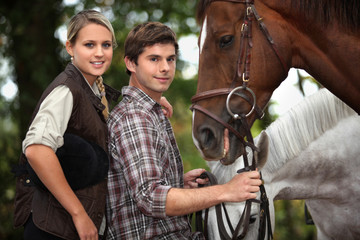 Young couple stood by horses