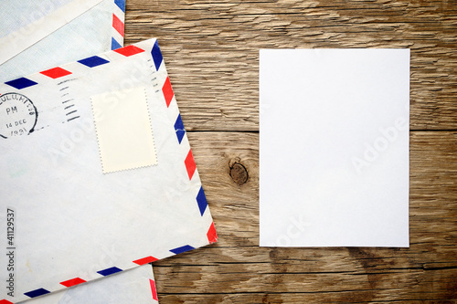 Old envelope and paper sheet on wooden background