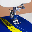 Sewing machine, thread and a yellow measuring tape