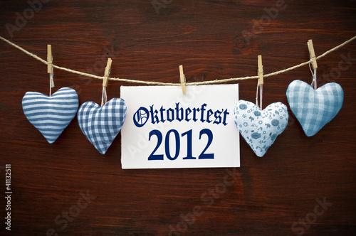 4 Stoffherzen in Blau auf Holzbrett mit Oktoberfest