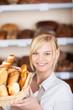 lächelnde bäckereiverkäuferin mit brotkorb