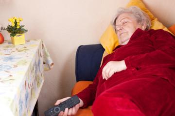 Seniorin liegt auf Sofa und schläft