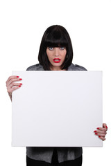 a woman looking amazed and showing a white panel