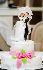 Figurines on top of wedding cake with roses decorations