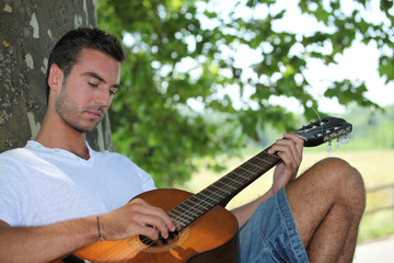 Man playing guitar under tree