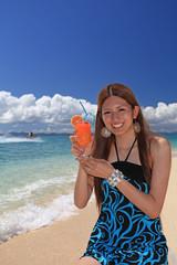 水辺でジュースを飲む笑顔の女性