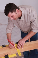 Man measuring wooden plank