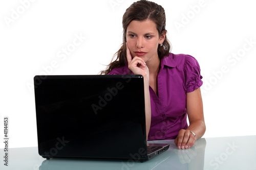 Pensive woman staring at her laptop