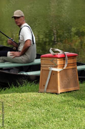 gentleman seated in boat fishing