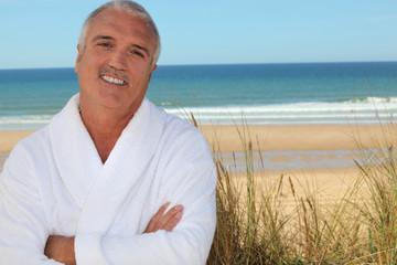 Man in bathrobe on the beach