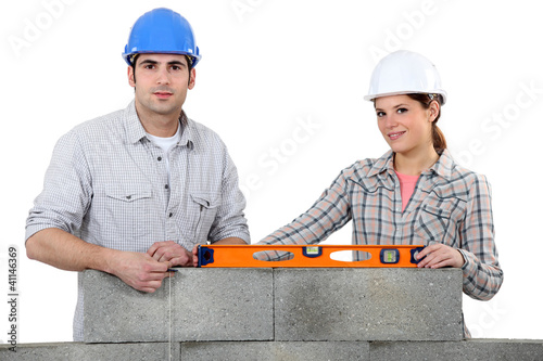 craftsman and craftswoman erecting a wall