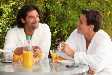 Two men eating breakfast in the garden