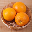 Three in wicker basket of oranges