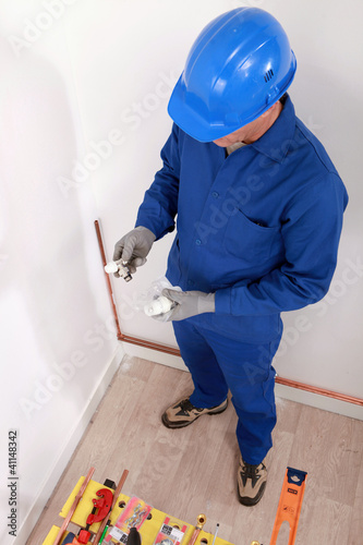 Plumber with pieces in the hands