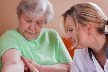 Altenpflegerin cremt Seniorin den Arm
