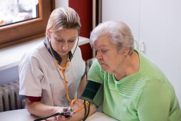Altenpflegerin misst Blutdruck bei Patientin
