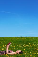 glückliche frau entspannnt mit einem buch draußen