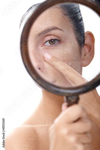 Young woman examining skin with magnifier