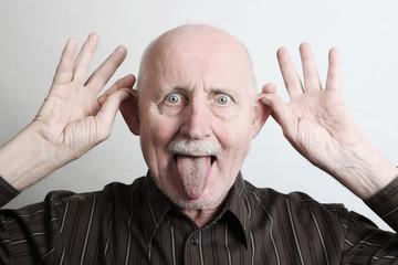 senior streckt die zunge aus