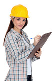 Female construction worker writing on her clipboard.