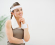 Fitness woman with towel on shoulders looking on copy space