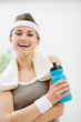 Fitness woman with towel on shoulders holding bottle of water