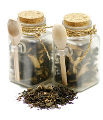 Tea leaves in transparent parisons with wooden spoon