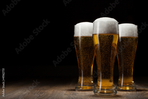 three glass beer on wooden table with copyspace