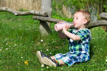 Kleiner Junge trinkt Fruchtmilch am Seeufer