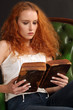 Beautiful redhead reading a bible