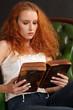 Beautiful redhead reading a bible