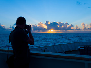 man taking photo of sunrise