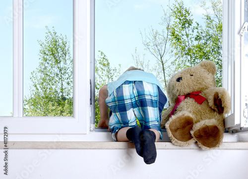 Junge beugt sich aus dem Fenster