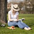 junge Frau mit Strohhut liest