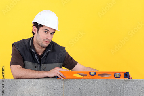 Builder with a spirit level on a wall