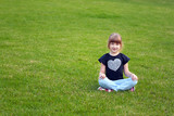 Cute smiling girl (7-years old) sitting on a lawn