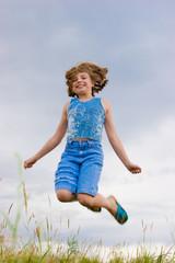 teenage girl jumping over green grass