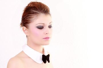 Visage d'une jolie fille maquillée avec un noeud papillon