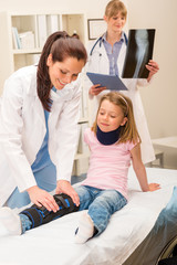 Pediatrician examining girl broken leg