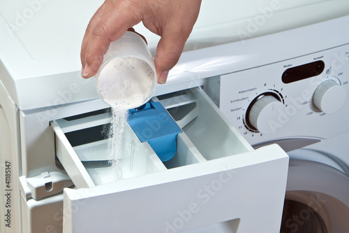 Man pours detergent into the washing machine