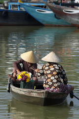 Couple of vietnamese woman paddling boat. Hoi An, Vietnam