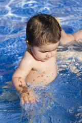 Newborn baby enjoying the summer in the pool