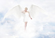Gorgeous young blond woman as angel in heaven