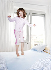 happy little girl jumping on a bed - morning