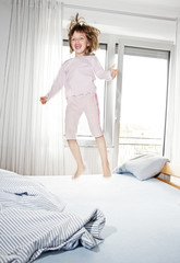 happy smilling little girl jumping on a bed