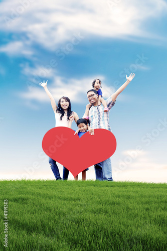 Happy Asian family in Meadow